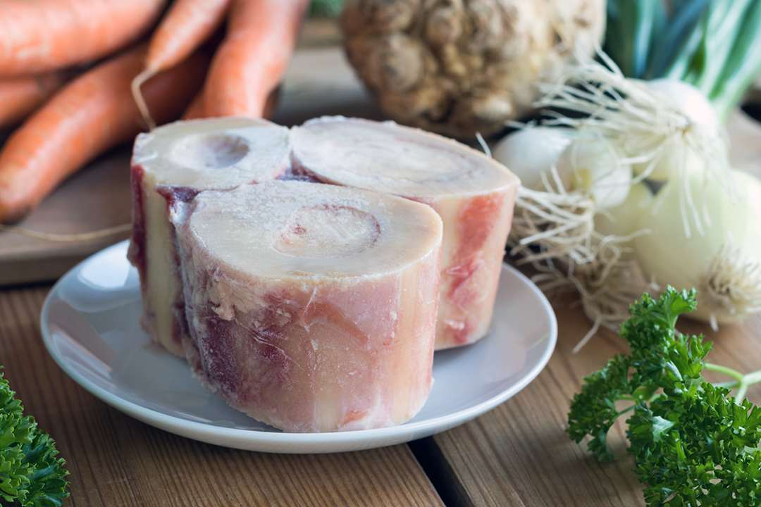 Ingredients for making a beef bone broth - marrow bones, carrots, onions, parsley, and celery root