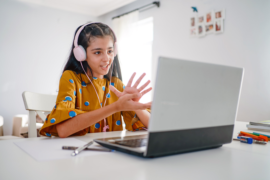 Teenage girl with headphones and laptop focused on online school class at home