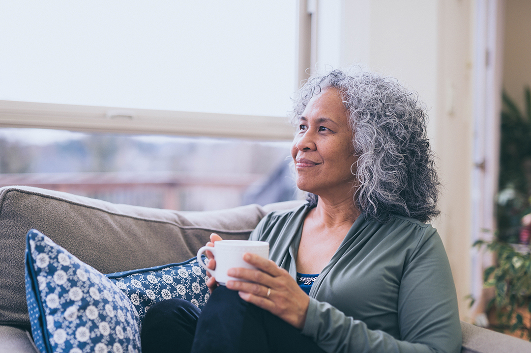Hawaiian women looking out window with a cup of coffee - Magnesium for better moods